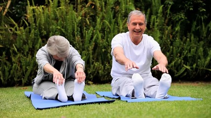 Mature couple stretching on gym mats