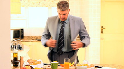 Man on phone rushing to eat breakfast and get off to work