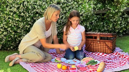 Young woman and her daughter eating fruits in the garden