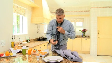 Man in kitchen receiving a call while rushing to go to work