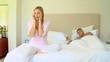 Young woman with a headache while husband sleeps