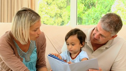 Couple showing picture book to baby