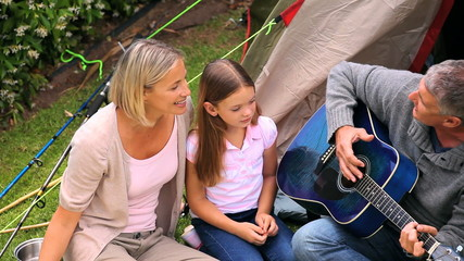 Father playing guitar with wife and children singing in garden