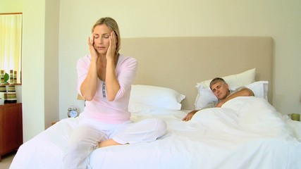 Young woman with a headache while husband sleeps