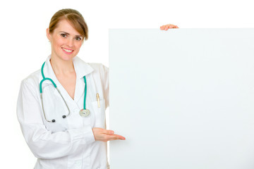 Smiling  medical doctor woman pointing on blank billboard