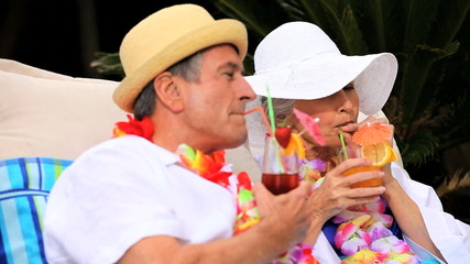 Mature couple with garlands enjoying cocktails