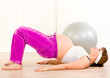 Pregnant female doing fitness exercises at living room.