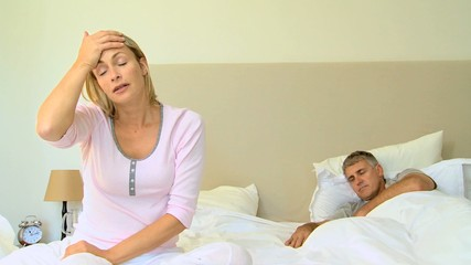 Young woman on bed with headache while husband sleeps