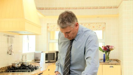 Man eating quickly and tightening his belt before leaving