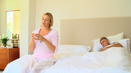 Young woman in bedroom taking a pill for a headache