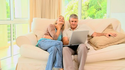 Couple on sofa enjoying a programme on their laptop