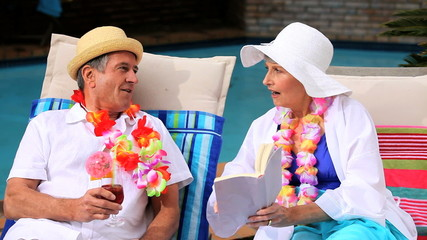 Couple with garlands by swimming pool laughing over a book