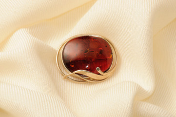 Golden brooch with amber on a shawl of cashmere and silk