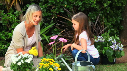 Young mother doing some gardening with daughter