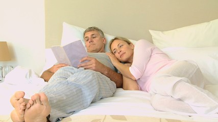Young wife on bed snuggling up to husband reading a book