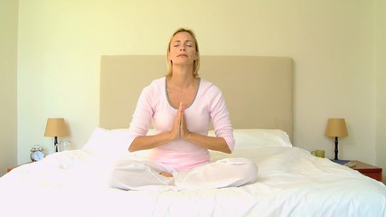 Blonde woman alone on bed doing yoga