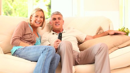 Couple watching thrilling event on TV