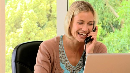 Young woman laughing on phone and working on a laptop