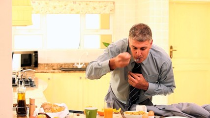 Man hurriedly taking a mouthful before leaving for work