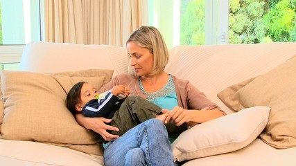 Young mother bottle feeding toddler
