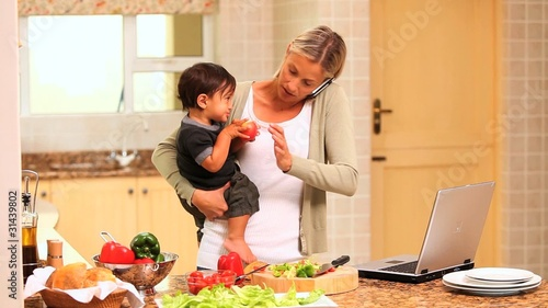 Mother coping with baby while cooking and using a laptop