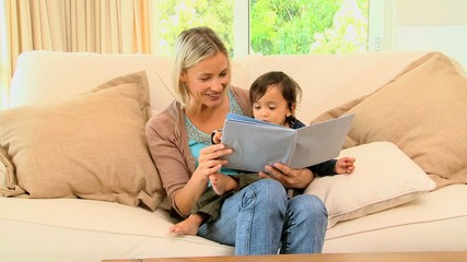 Young mother and baby  looking at picture book