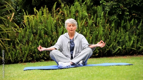 Mature  woman doing yoga outdoors on a mat
