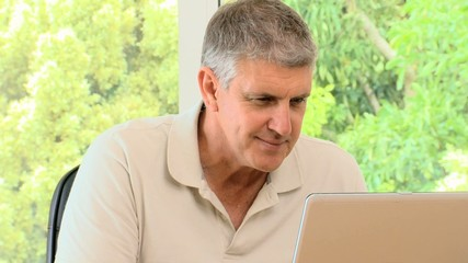 Mature man working on his laptop and then posing
