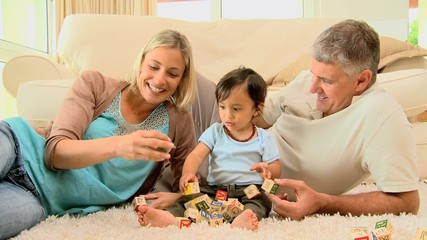 Doting parents laughing with baby on carpet