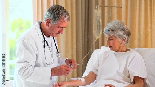 Doctor fixing up a drip-feed for patient in hospital bed