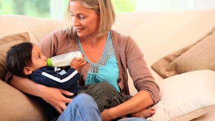 Relaxed mother bottle-feeding her child