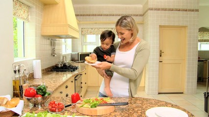 Woman with son in her armsin kitchen