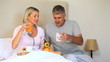 Wife enjoying breakfast in bed brought by husband