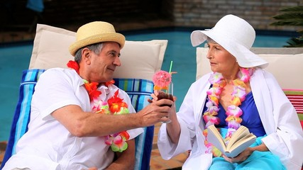 Mature couple enjoying their cocktails by the pool