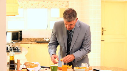 Businessman in suit hurriedly taking his breakfast