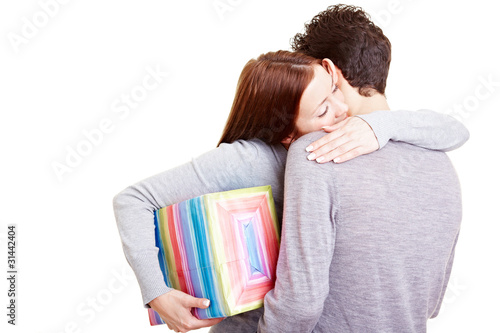 Frau mit Geschenk umarmt Mann