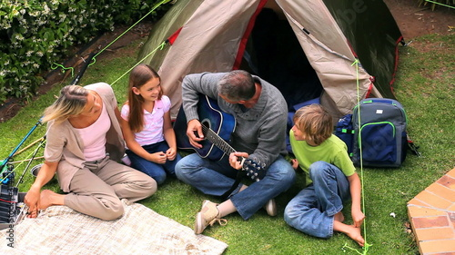 Father playing guitar in front of his family
