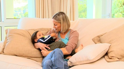 Blonde haired woman bottle-feeding her child