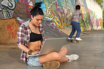 ragazza con portatile in skatepark