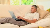 Man lying on coch working on his laptop