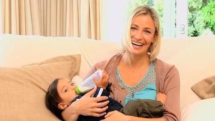 Woman bottle-feeding her son
