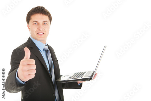 Young businessman with laptop in hand show thumb