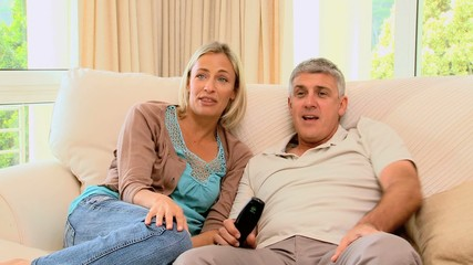 Attractive couple watching a match on the tv