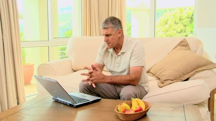 Mature man getting good news on his laptop