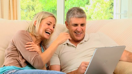 Attractive couple looking and laughing at laptop