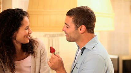 Man giving a strawberry to his wife