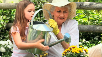 Young girl with her grandmother watering a plant
