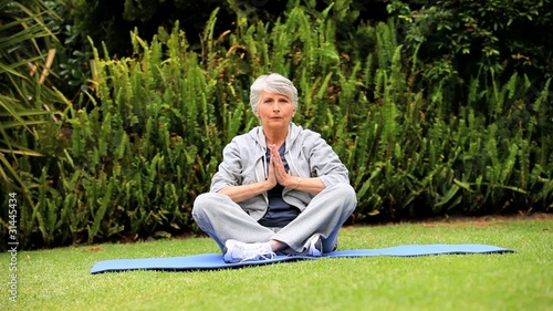 Mature woman doing yoga in garden