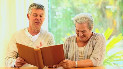 Retired couple looking at an album