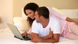 Young couple lying on their bed using a laptop